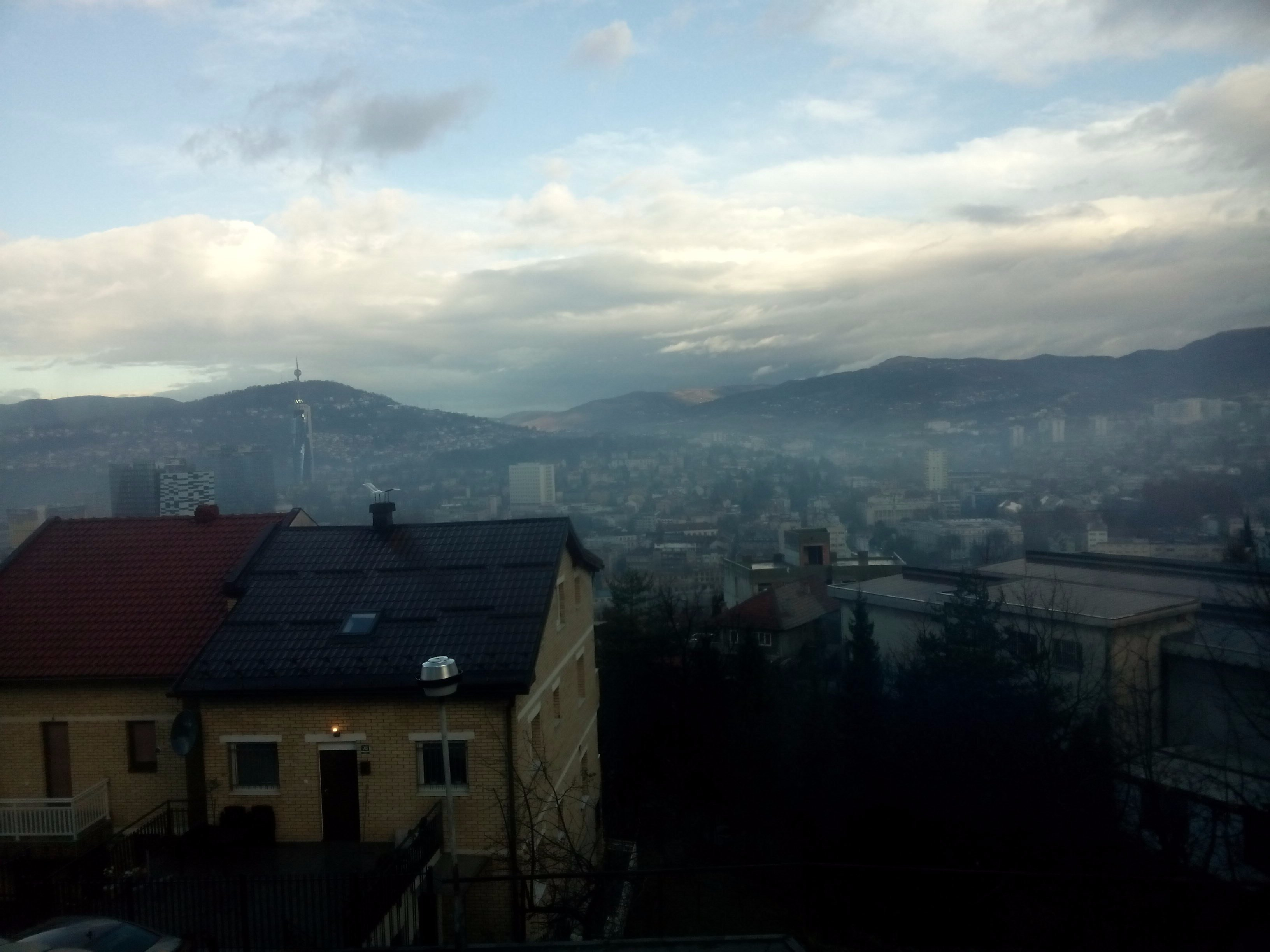 A view over Sarajevo city center from the mountainside with some clouds and a little blue sky